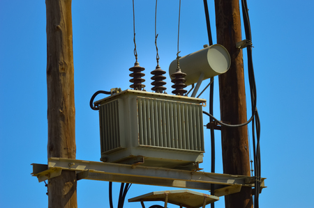 Electric transformer on wooden pylons with an arrival and several departures and countless recreations Stock Photo