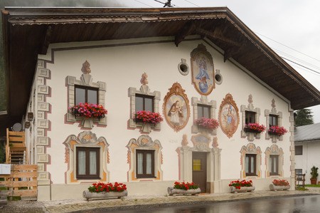 Traditional architecture in the Austrian Tyrol with paintings on the window and door frames in the Tyrol mountains in Austria.