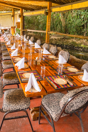 Table set on a jungle-colored terrace in a tropical environment in a restaurant in Nairobi, Kenya Stock Photo