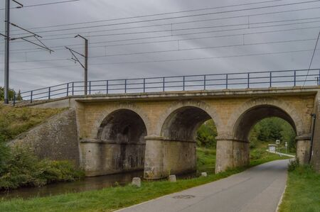 Railway bridge with three arches, two for the river of the tone and one for the tarmaker road in the city of Virton in the province of Luxembourg in Belgium