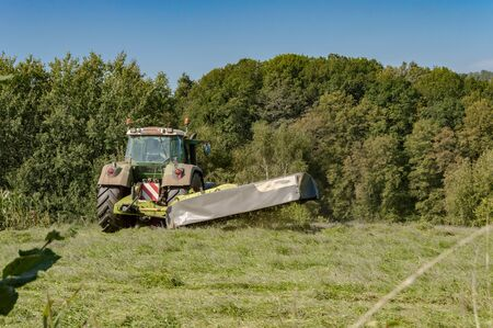 Last mowing of a tractor in a meadow of the gaume near Virton in Belgium