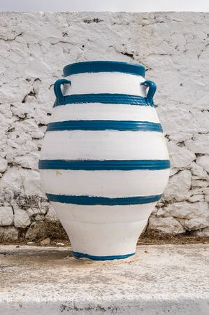 Old blue and white amphora lay on the ground in front of a white wall on the island of Crete Banco de Imagens