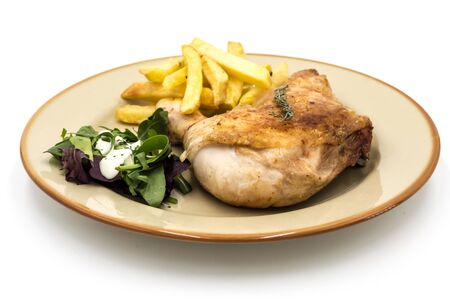 Roasted chicken leg with fries and vegetables on white background