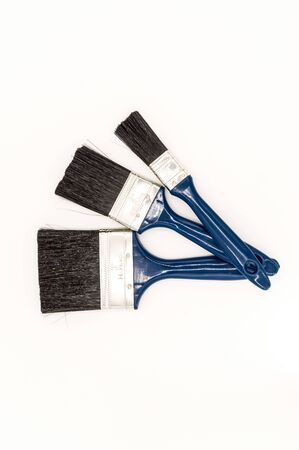 Three paint brushes with blue colored handles on an isolated white background