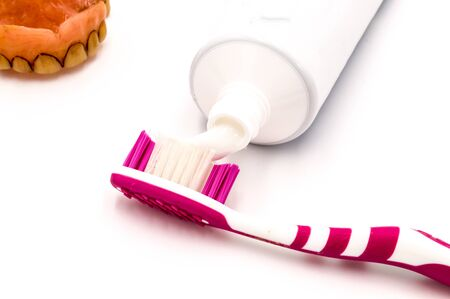 Toothpaste on a toothbrush with a dirty denture on a white background