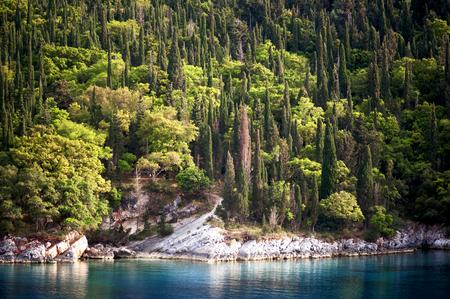 The beautiful azure waters of the Ionian Sea and Mediterranean cypress trees at Foki Bay near Fiskardo on the east coast of the Greek island of Kefalonia. Stock Photo