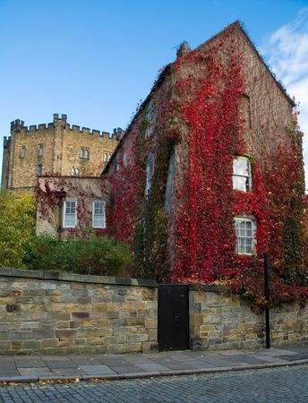 durham: red ivy covered house with durham castle in background