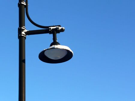 Street lamp covered in snow over a clear blue sky photo