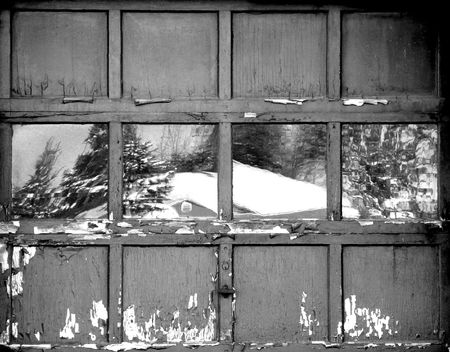 Old worn out door in black and white with a rural winter scene reflecting in the window Stock Photo - 2220741