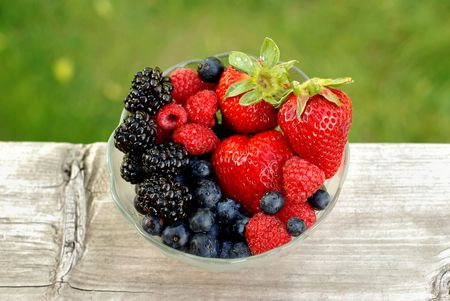 Bowl of mixed berries outdoors with a contrasting background Stock Photo