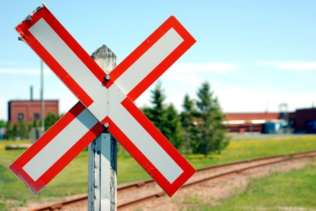 Old railroad crossing stop sign in a rural scene with shallow focus photo