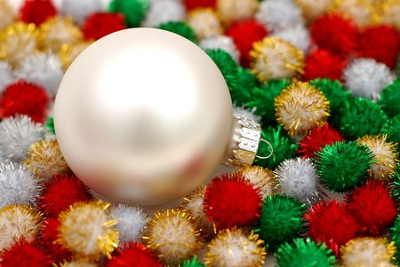 Silver christmas bauble resting on colorful puff ball decorations