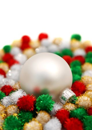 Silver Christmas bauble resting on colorful puff ball decorations over a white background Stock Photo