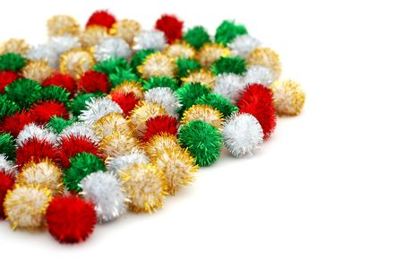 Pile of small sparkling festive deocation puff-balls on a white background