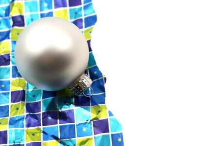 Holiday decoration ornaments resting over wrinkled used torn wrapping paper on white background photo