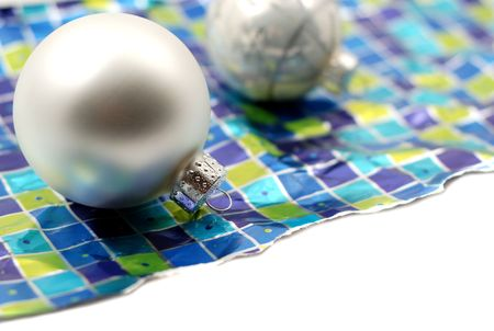 Holiday decoration ornaments resting over wrinkled used torn wrapping paper on white background
