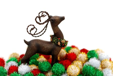 Reindeer ornament and colorful puff ball decorations over a white background