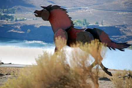 Metal horse sculpture high up on a ridge overlooking a river and valley