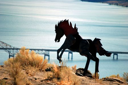 Metal horse sihlouette high up overlooking a river landscape
