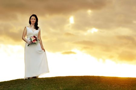 bride standing on hill at sunset