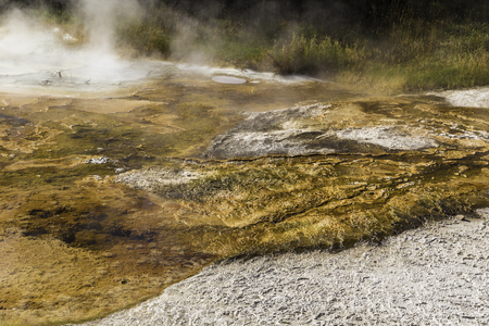 alien landscape: Yellowstone National Park, Wyoming, United States September 20, 2014 – Geothermal activity in Yellowstone creating a steamy pool of colors similar to an alien landscape.