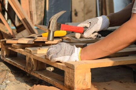 The carpenter is nailing the wood.