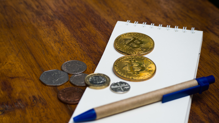 Bitcoin coin with Pound money Put on a note and a pen. Concept  take note of the volatility of digital money against the euro. Stock Photo