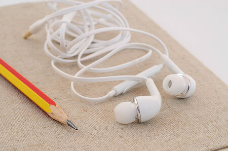 Modern portable audio earphones on calico notepad dairy book photo
