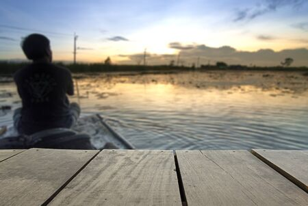 a wonderful world: Defocus and blur image of terrace wood and Lonely man sitting on boat at beautiful lake near home for background usage Stock Photo