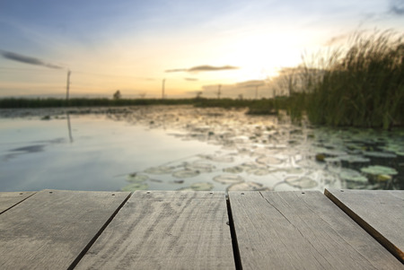 a wonderful world: Defocus and blur image of terrace wood and Beautiful lake inside home in sunset time background usage Stock Photo