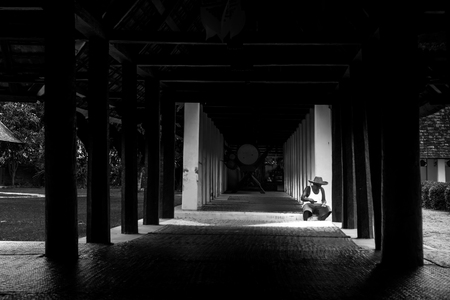 sit around: Old man sit under roof alone in home with dramatic style
