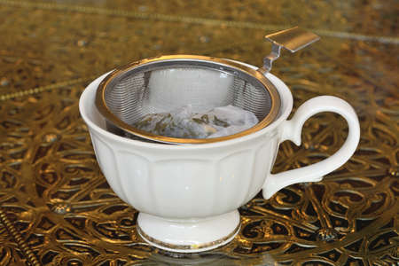 tea strainer: Vintage tea strainer and tea ready in cup Stock Photo