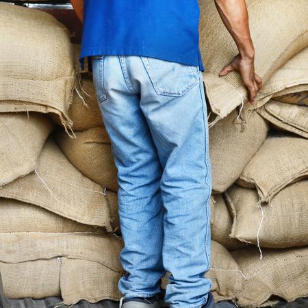 storekeeper: Workers hands lifting Hemp sacks containing rice in warehouse