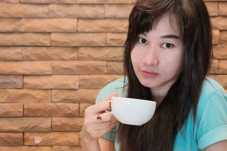 cappaccino: Beautiful Woman Drinking Coffee front of brick wall background Stock Photo