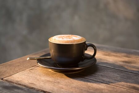 Hot cappuccino coffee cup on wooden table Banco de Imagens
