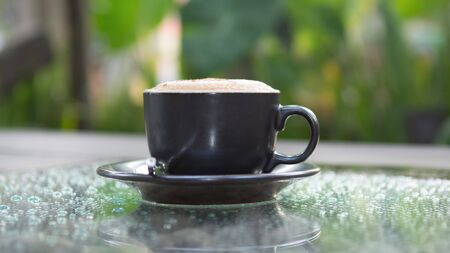dewdrop: Hot cappuccino coffee cup on grass table in garden with dewdrop foreground