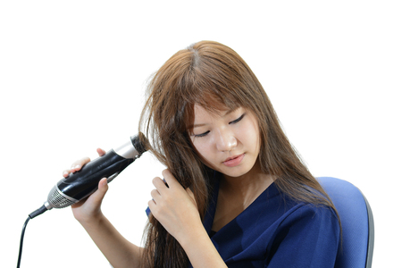 Hair Care. Woman Drying Beautiful Long Straight Hair Using Dryer. Portrait Of Attractive Girl Model With brunette Hair Using Hairdryer, Round Brush For Hairdressing. Hairstyle Concept. Stock Photo