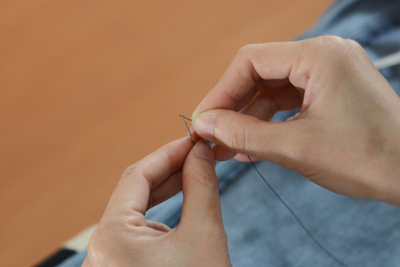 Manual thread the needle by hands as background