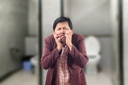 Asian Businessman feel pain with constipation and crumpled face in front of the bathroom Stock Photo
