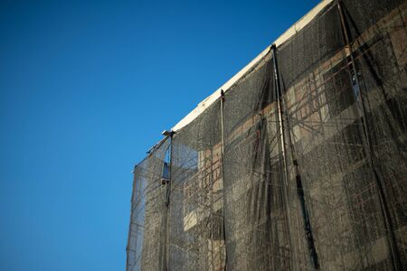 Building between under construction use shading net cover scaffolding for protect dust and particulate matter Stockfoto