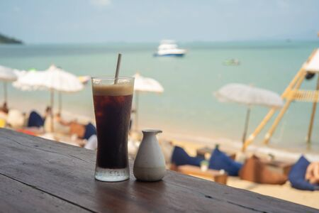 Cold black coffee and syrup over terrace wood with beach and sea background