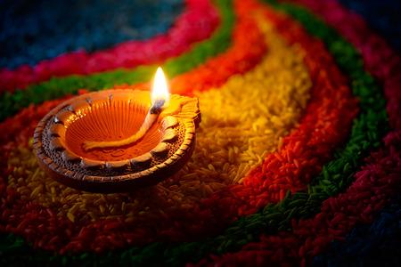 Traditional diya lamp lit on colorful rangoli Archivio Fotografico