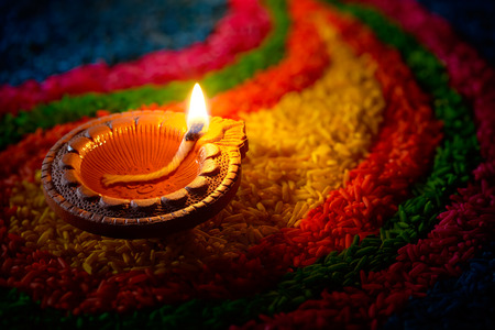 the festival: Traditional diya lamp lit on colorful rangoli Stock Photo