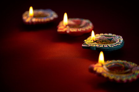 and  celebrate: Colorful clay diya lamps lit during diwali celebration