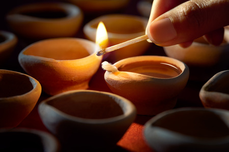 Hand holding a matchstick lighting diya lamps during diwali celebration