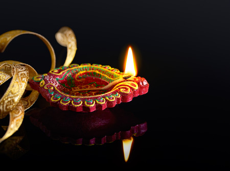 red oil lamp: Colorful clay diya lamp with reflection Stock Photo