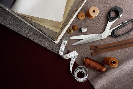 kit de costura: Tijera, botones, cremallera, cinta métrica, hilo y dedal en telas Foto de archivo