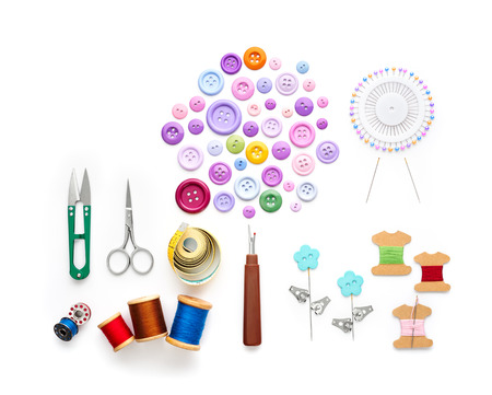 Overhead view of sewing tools and accessories on white background Imagens