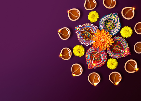 diyas: Colorful clay diya lamps with flowers on purple background