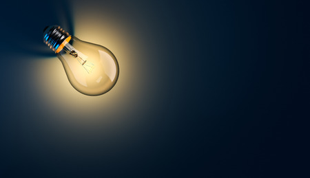 creative power: Glowing light bulb with long shadow on blue background Stock Photo